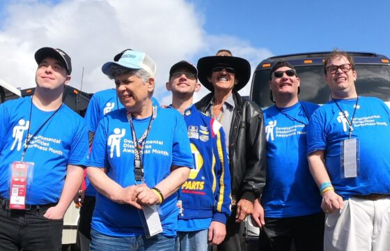 Richard Petty posing with people wearing blue shirts